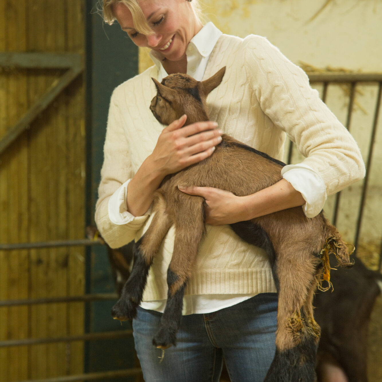 Sarah Sharratt, host of Cooking Channel's UpRooted holds a baby goat in rural France